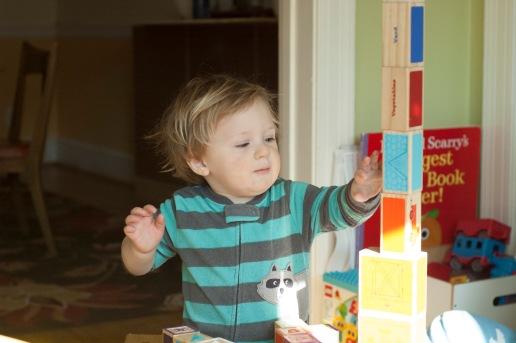 little boy building a block tower
